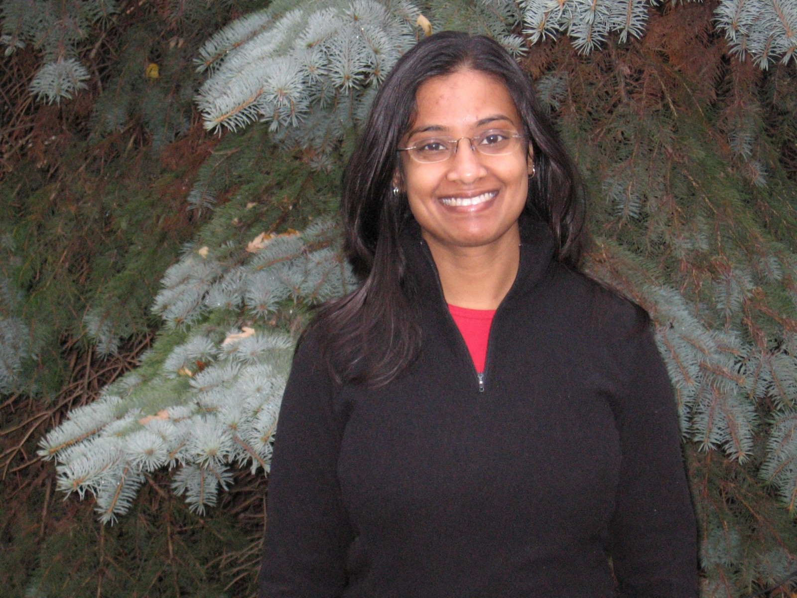 Dr. Anurani Persaud in front of pine trees.
