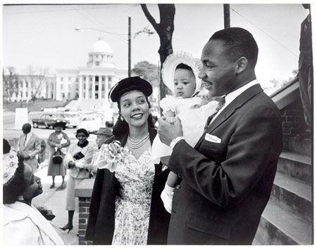 Dr. Martin Luther King Jr. holds his infant daughter as he stands beside his wife smiling.
